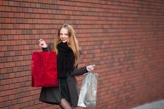 Продажа, защита интересов потребителя и концепция людей - счастливые молодые красивые женщины держа хозяйственные сумки, идя дале Стоковые Фото