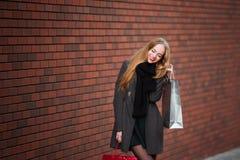 Продажа, защита интересов потребителя и концепция людей - счастливые молодые красивые женщины держа хозяйственные сумки, идя дале Стоковое Фото
