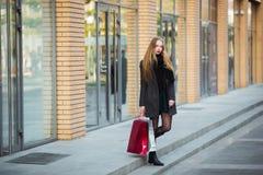Продажа, защита интересов потребителя и концепция людей - счастливые молодые красивые женщины держа хозяйственные сумки, идя дале Стоковое фото RF