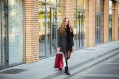 Продажа, защита интересов потребителя и концепция людей - счастливые молодые красивые женщины держа хозяйственные сумки, идя дале Стоковое Изображение