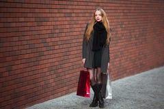Продажа, защита интересов потребителя и концепция людей - счастливые молодые красивые женщины держа хозяйственные сумки, идя дале Стоковое Изображение RF