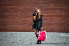Продажа, защита интересов потребителя и концепция людей - счастливые молодые красивые женщины держа хозяйственные сумки, идя дале Стоковые Фотографии RF
