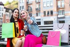 Продажа и туризм, счастливая концепция людей - красивые женщины с хозяйственными сумками стоковые фотографии rf