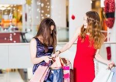 Продажа, покупки, туризм и счастливая концепция людей - 2 красивых женщины смотря внутренние хозяйственные сумки в магазине Стоковое Изображение