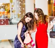 Продажа, покупки, туризм и счастливая концепция людей - 2 красивых женщины смотря внутренние хозяйственные сумки в магазине Стоковые Фото