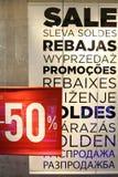 Продажа подписывает внутри окно магазина одежды Стоковое фото RF