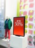 Продажа подписывает внутри окно магазина с манекеном ` s мальчика Стоковое фото RF