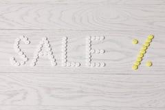 Продажа слова сделанная пилюлек на таблице Стоковые Фотографии RF