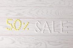 Продажа слова сделанная пилюлек на таблице Стоковая Фотография RF