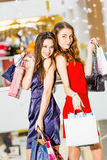 Продажа, туризм, покупки и счастливая концепция людей - 2 красивых женщины с хозяйственными сумками в торговом центре Стоковые Фото