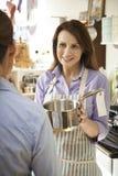 Продажи ассистентские в магазине Homeware показывая лоток клиента Стоковые Фотографии RF