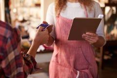 Продажи ассистентские с читателем кредитной карточки на таблетке цифров стоковое фото rf