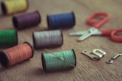 Проденьте нитку с иглой и ножницами на деревянном столе, винтажном тоне Стоковое фото RF