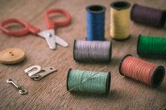 Проденьте нитку с иглой и ножницами на деревянном столе, винтажном тоне Стоковое Изображение RF