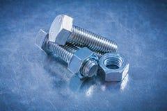 Продетые нитку детали болта с винт-гайками на металлической предпосылке жульничают Стоковая Фотография RF
