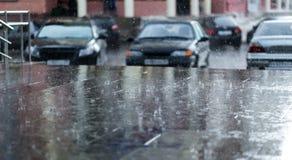 Проливной дождь падает на асфальт с припаркованной предпосылкой автомобилей Стоковое фото RF