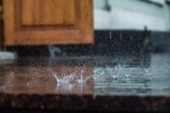 Проливной дождь падает падать на асфальт города во время ливня Стоковые Фотографии RF