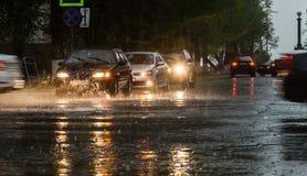 Проливной дождь ударяя конкретный тротуар пока автомобили управляют мимо Селективный фокус Стоковое Фото