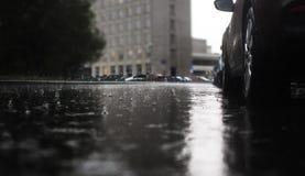 Проливной дождь ударяя конкретный тротуар пока парковать автомобилей Стоковые Изображения