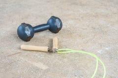 Прыгая веревочка и dumbell для тренировки на поле цемента Стоковое фото RF