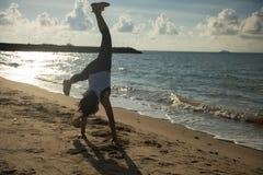 Прыжок кувырком девушки спортсмена на пляже на восходе солнца Стоковое Изображение