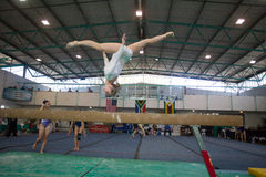 Прыжок кувырком сальто антенны луча девушки гимнаста  Стоковая Фотография RF