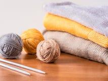 Пряжа, иглы и knitwear на деревянном столе Стоковое Изображение
