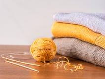 Пряжа, иглы и knitwear на деревянном столе Стоковые Фото