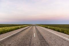 Прямая дорога через захолустье Австралии, после красивого захода солнца стоковая фотография