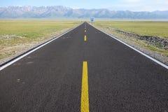 Прямая дорога с горами снега Стоковая Фотография