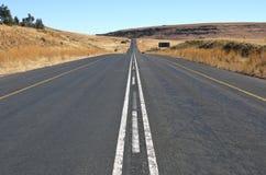 Прямая сельская дорога асфальта в оранжевом освободившееся государство, Южной Африке Стоковая Фотография RF