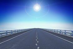 Прямое шоссе с следами ноги и направлять играют главные роли над горизонтом стоковое фото rf