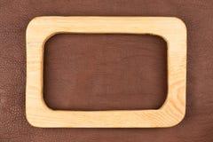 Прямоугольная доска светлой древесины лежит на коричневой естественной коже Текстура дерева Стоковое Фото