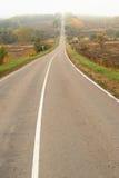 Прямо опорожните туманную дорогу идя вверх в осень в стране Стоковая Фотография