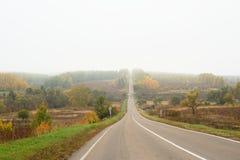 Прямо опорожните туманную дорогу идя вверх в осень в стране Стоковые Фотографии RF