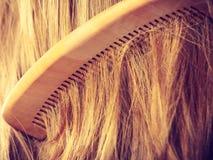 Прямые коричневые волосы с деревянным крупным планом гребня Стоковая Фотография