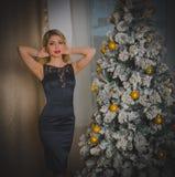 Пряная девушка в черном платье на Рожденственской ночи самостоятельно Стоковое Изображение