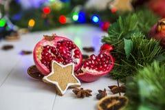 Пряник в форме звезд, гранатовое дерево отрезка красное, циннамон, высушил лимоны на белой таблице на предпосылке гирлянды и свет Стоковое Изображение