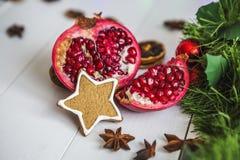 Пряник в форме звезд, гранатовое дерево отрезка красное, циннамон, высушил лимоны на белой таблице на предпосылке гирлянды и свет Стоковое Фото