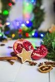 Пряник в форме звезд, гранатовое дерево отрезка красное, циннамон, высушил лимоны на белой таблице на предпосылке гирлянды и свет Стоковые Изображения