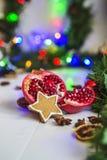 Пряник в форме звезд, гранатовое дерево отрезка красное, циннамон, высушил лимоны на белой таблице на предпосылке гирлянды и свет Стоковое фото RF