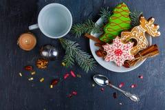 Пряник рождества, душистый циннамон и jn ручек гайки плита, следующий палец ноги a и горящая свеча Стоковые Изображения