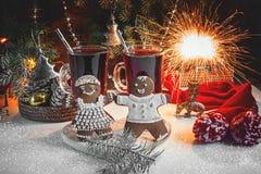 Пряник рождества и 2 стекла обдумыванного вина для таблицы рождества на предпосылке гирлянд и хворостин рождества Стоковые Фото