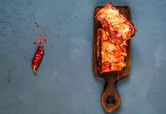 Пряные горячие зажаренные запасные нервюры от BBQ служили с перцем горячего chili на деревянной доске на голубой предпосылке бето стоковая фотография rf
