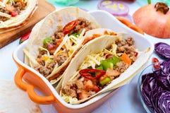 Пряные мексиканские тако с семенить мясом, помятые фасоли, овощи, заскрежетанный сыр Стоковая Фотография RF