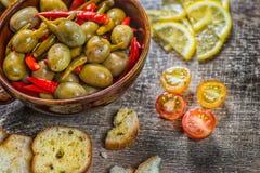 Пряные черные оливки и перец в шаре Замаринованные wi зеленых оливок Стоковые Фото