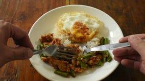Пряный пошевелите зажаренную свинину с карри фасоли двора длинным покрывая яйцо на рисе черпая ложкой и вилкой для еды сток-видео