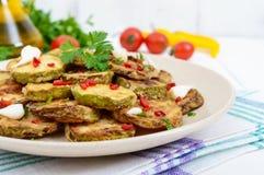 Пряный салат зажаренных кусков цукини и молодого чеснока, специй, трав и красного перца на плите Стоковое Изображение RF