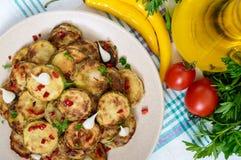 Пряный салат зажаренных кусков цукини и молодого чеснока, специй, трав и красного перца на плите Стоковые Фотографии RF
