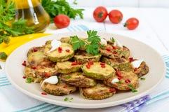 Пряный салат зажаренных кусков цукини и молодого чеснока, специй, трав и красного перца на плите Стоковое Фото